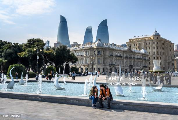 Couple sits on a fountain in the center of Baku, with the Flame Tower seen in the background, on March 22, 2019.