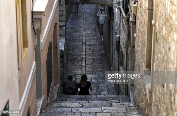 A couple sits on a stairs in the walled Old Town of Dubrovnik in Croatia taken on September 2 2018