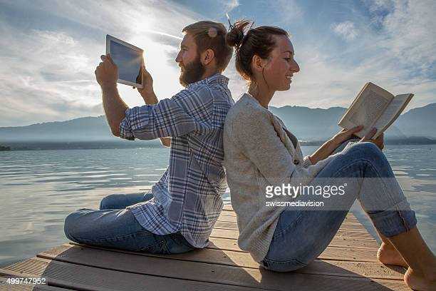 Couple sits on jetty above lake, uses book/digital tablet
