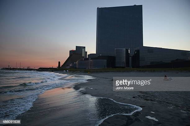 A couple sits on the beach near the closed and darkened Revel casino on August 28 2015 in Atlantic City New Jersey After new casinos opened in...