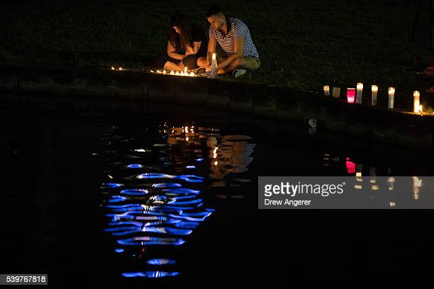 A couple sits on the edge of Lake Eola where candles were placed for the victims of the nightclub shooting June 12 2016 in Orlando Florida The...