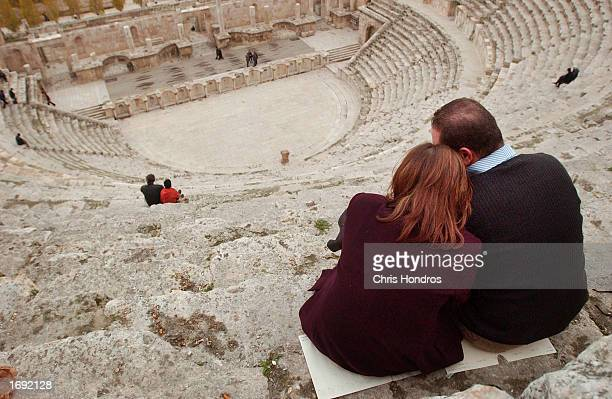 A couple sits on the top step looking over a Roman ampitheater December 17 2002 in Amman Jordan Jordan is home to dozens of worldclass historic sites...