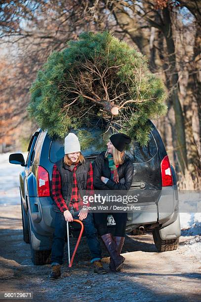 A couple sits on their vehicle with their fresh cut Christmas tree at a Christmas tree farm