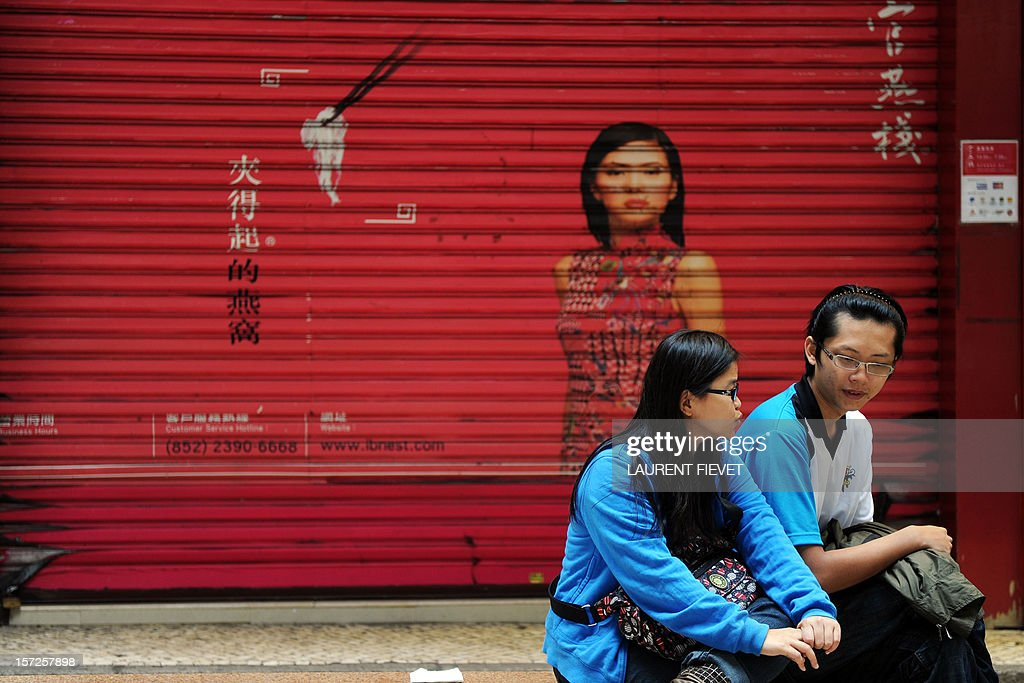 A couple sits talking in front of a closed shop in Macau on December 1, 2012