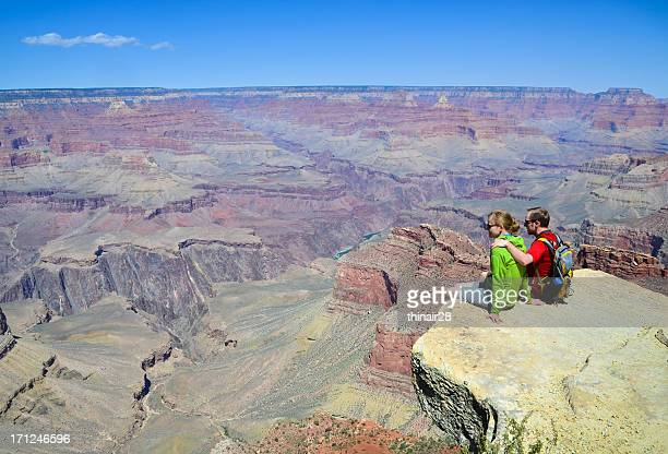 Couple sitting above Grand Canyon