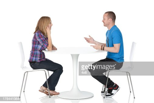 Couple Sitting Across From One Another At A Table High Res
