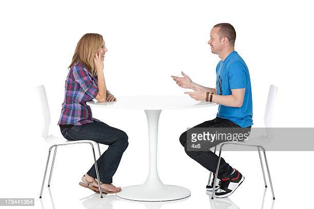 Couple sitting across from one another at a table