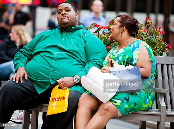 couple sitting and talking at rockefeller plaza, new york - fat black man stock photos and pictures