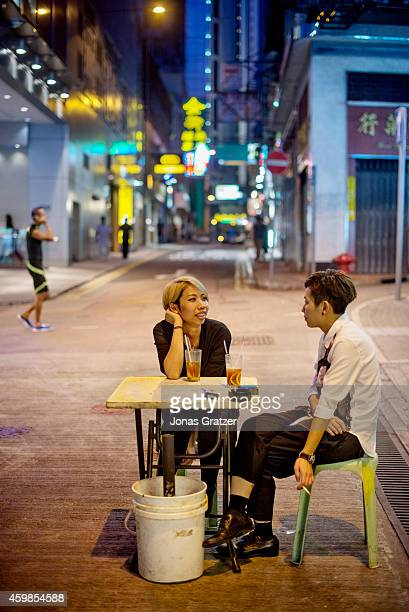 A couple sitting around a table of a streetfood restaurant in the city of Hong Kong