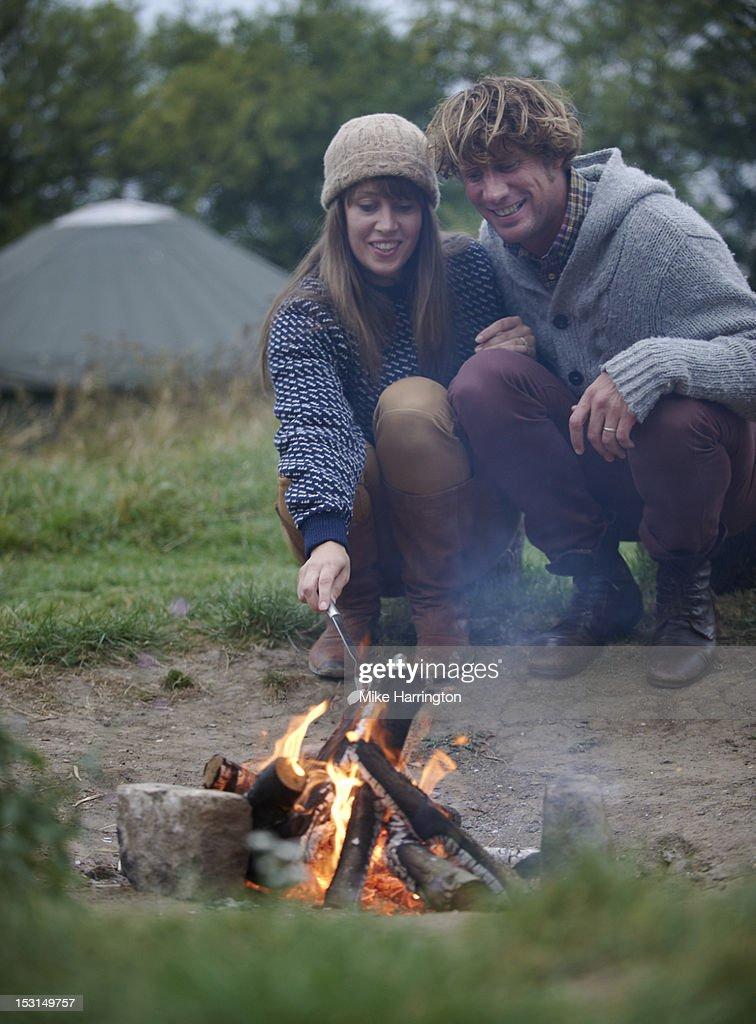Couple sitting around fire toasting marshmallows. : Bildbanksbilder