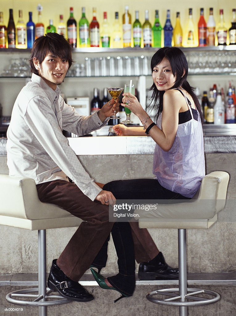 Couple Sitting at a bar Making a Toast With Cocktails : Stock Photo