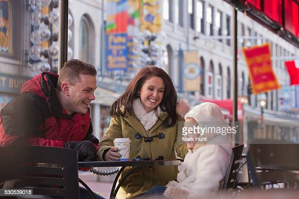 Couple sitting at a cafe with their daughter at Quincy Market, Boston, Massachusetts, USA