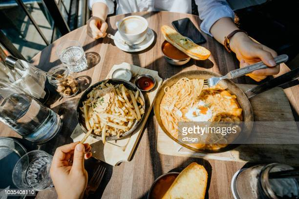 couple sitting at a table by the window sharing freshly prepared meal with french fries and pasta in a restaurant - fries stock-fotos und bilder
