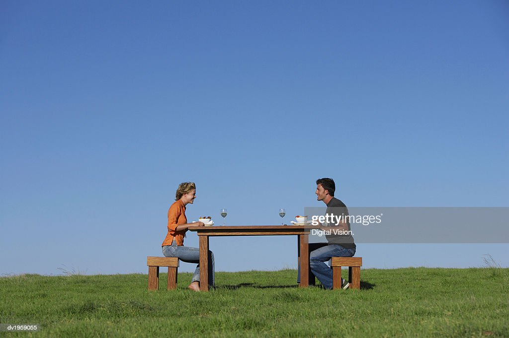 Couple Sitting at a Table on the Grass for Breakfast : Stock Photo