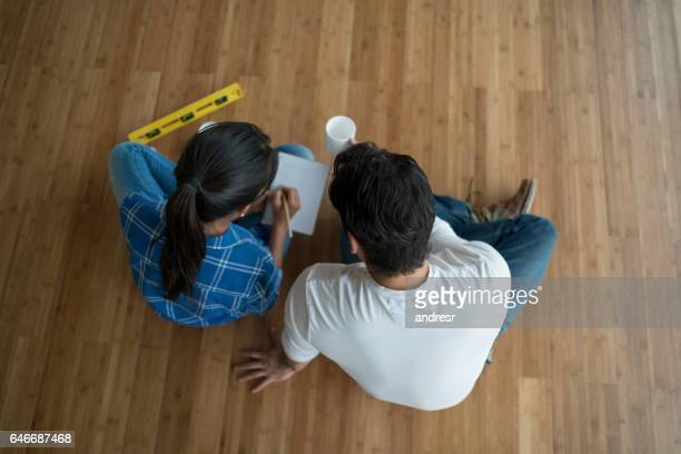 Couple sitting at an empty room talking about interior design