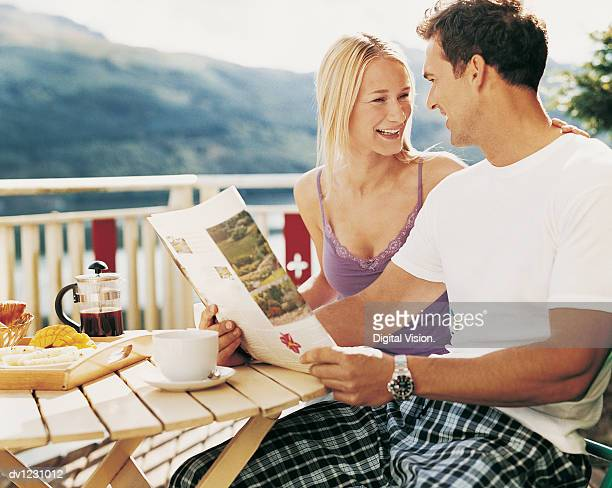 Couple Sitting at an Outdoor Breakfast Table, Man Holding a Magazine