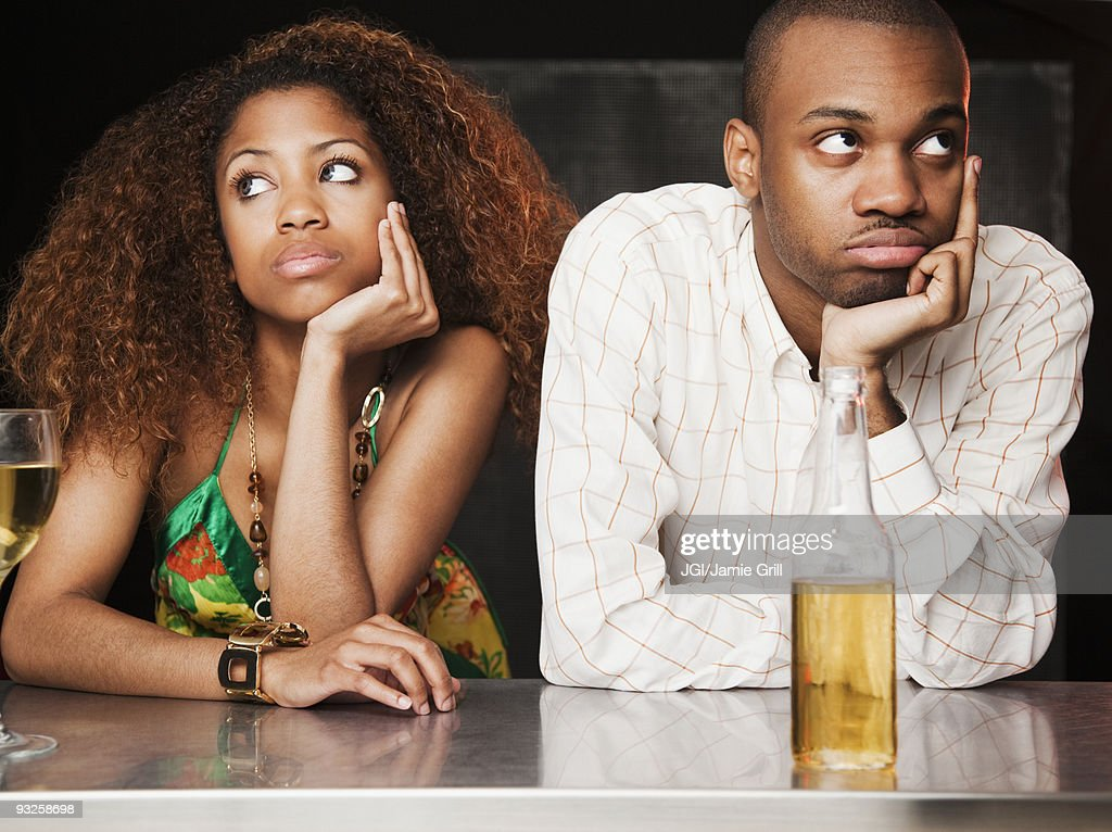Couple sitting at bar and looking irritated : Stock Photo