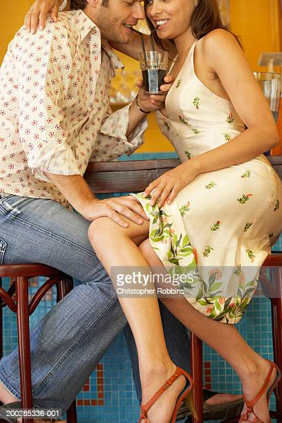 couple sitting at bar in cafe, man touching woman's knee, smiling - man touching womans leg stock photos and pictures