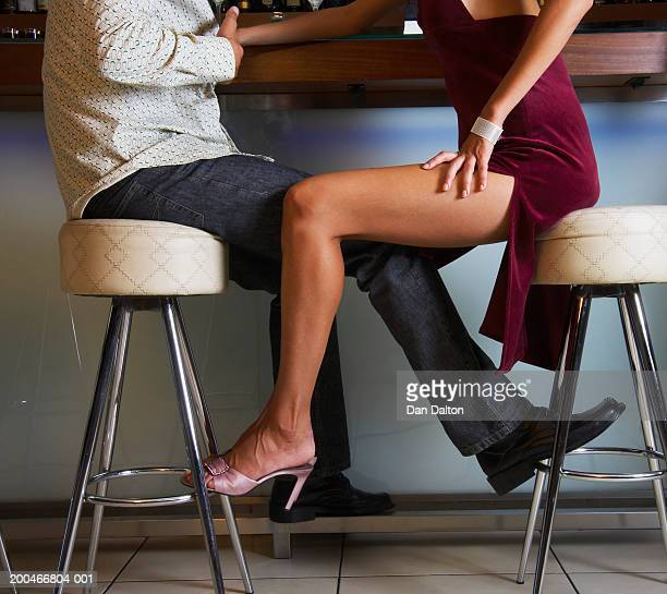 couple sitting at bar, low section, side view - man touching womans leg stock photos and pictures