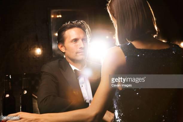 couple sitting at bar - タキシード ストックフォトと画像