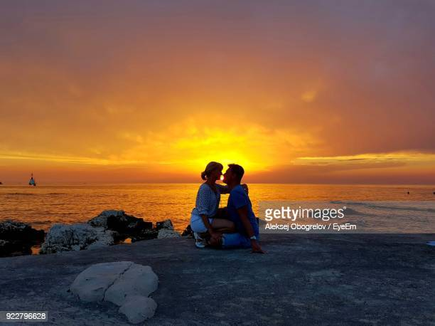 Couple Sitting At Beach Against Sky During Sunset