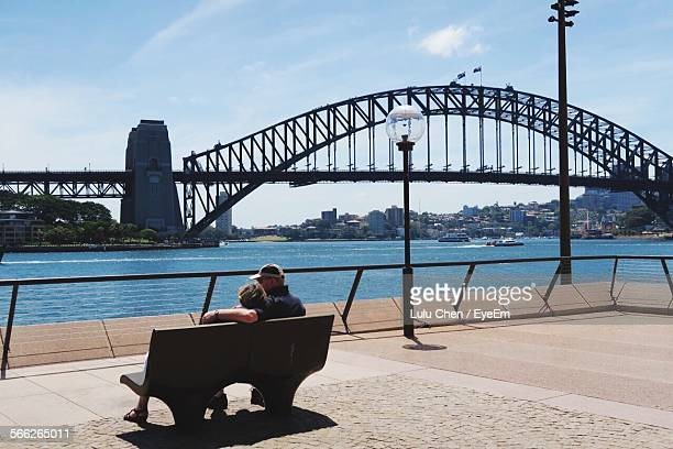 Couple Sitting At Bench In Front Of Sydney Harbor Bridge And River Against Sky