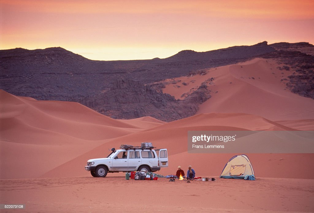 Couple Sitting At Campfire In Desert Next To Suv And Tent High Res Stock Photo Getty Images