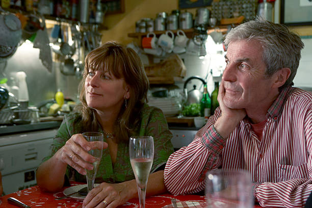 Couple sitting at kitchen table looking off camera