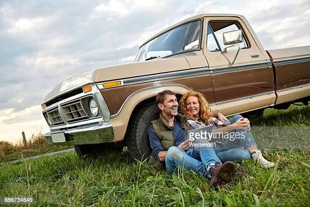 couple sitting at pick up truck with tablet - partire bildbanksfoton och bilder
