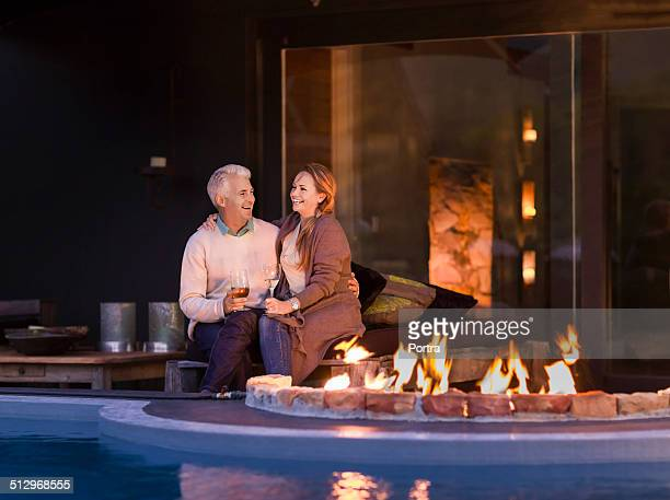 Couple sitting at poolside by fire pit at night