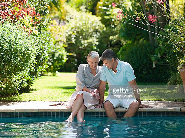 Couple assis au bord de piscine dans le jardin
