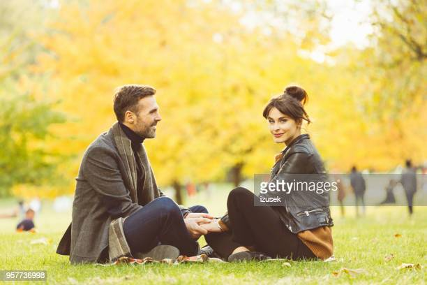 couple sitting at public park on autumn weekend - izusek stock pictures, royalty-free photos & images