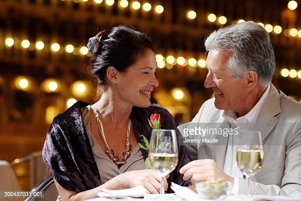 couple sitting at restaurant in square, smiling at each other, night - イブニングウェア ストックフォトと画像