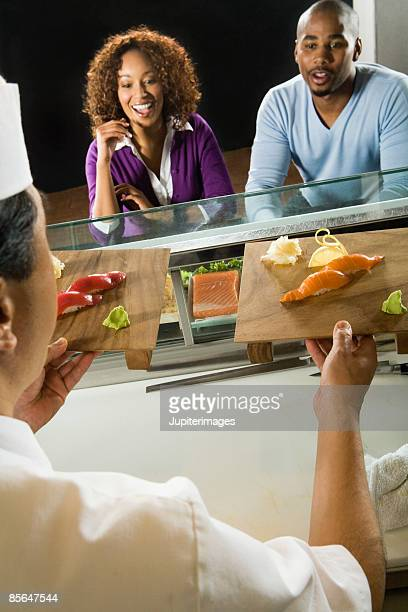 couple sitting at sushi bar - wasabi sauce stock pictures, royalty-free photos & images