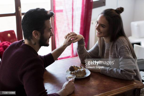 Couple sitting at table holding hands, drinking coffee
