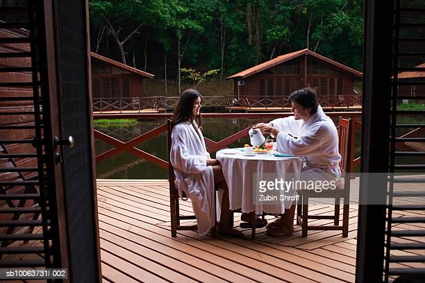 Couple sitting at table in balcony, man pouring tea in teacup, side view
