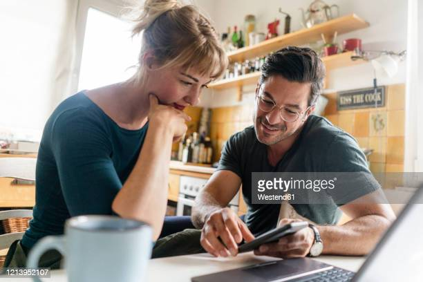 couple sitting at table in kitchen using smartphone - mid volwassen stockfoto's en -beelden
