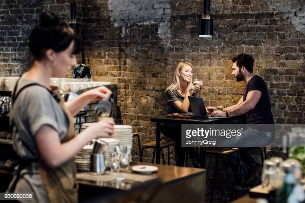 Couple sitting at table in modern cafe with waitress preparing drink in foreground
