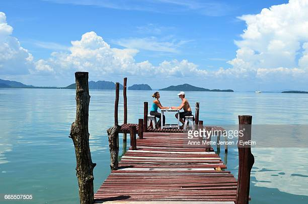 Couple Sitting At Table On Pier