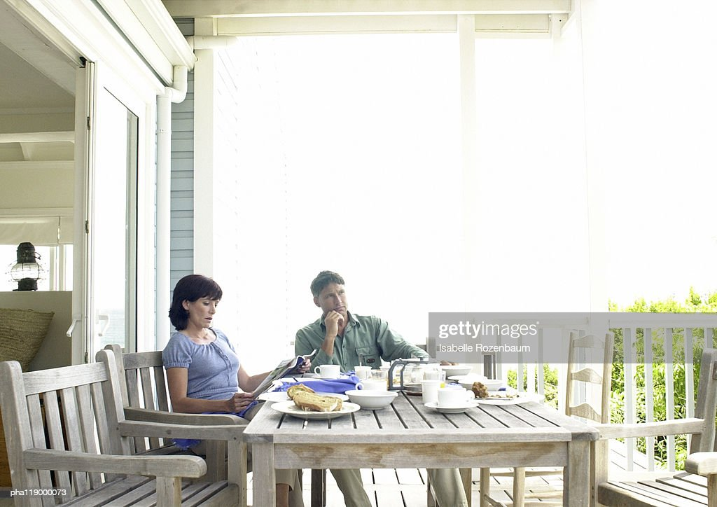 Couple sitting at table, outside : Stockfoto