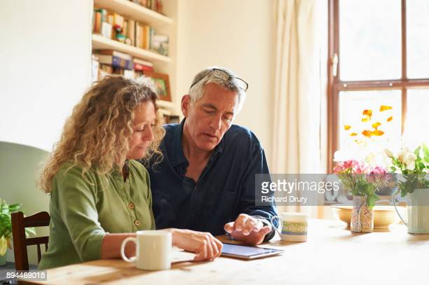 couple sitting at table using digital tablet - 50 59 years stock pictures, royalty-free photos & images