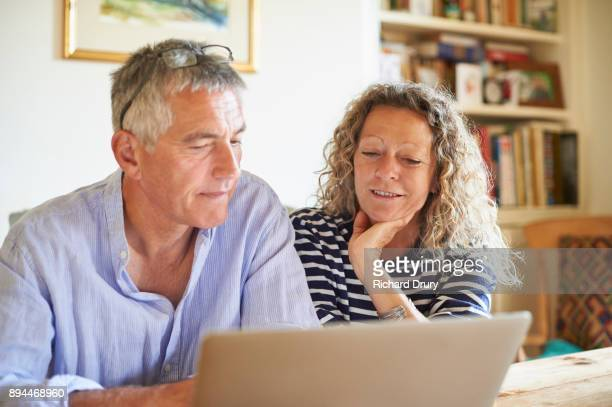 Couple sitting at table using laptop