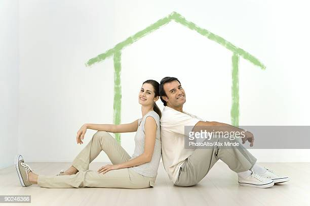 Couple sitting back to back in front of an outline of a house painted on wall