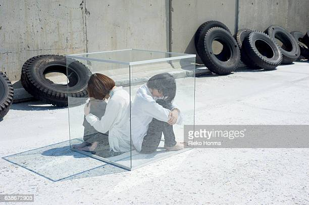 A couple sitting back to back in the glass cube