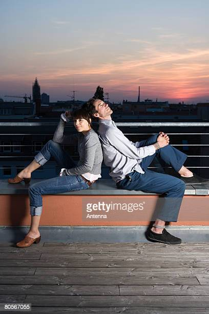 A couple sitting back to back on a rooftop terrace at night