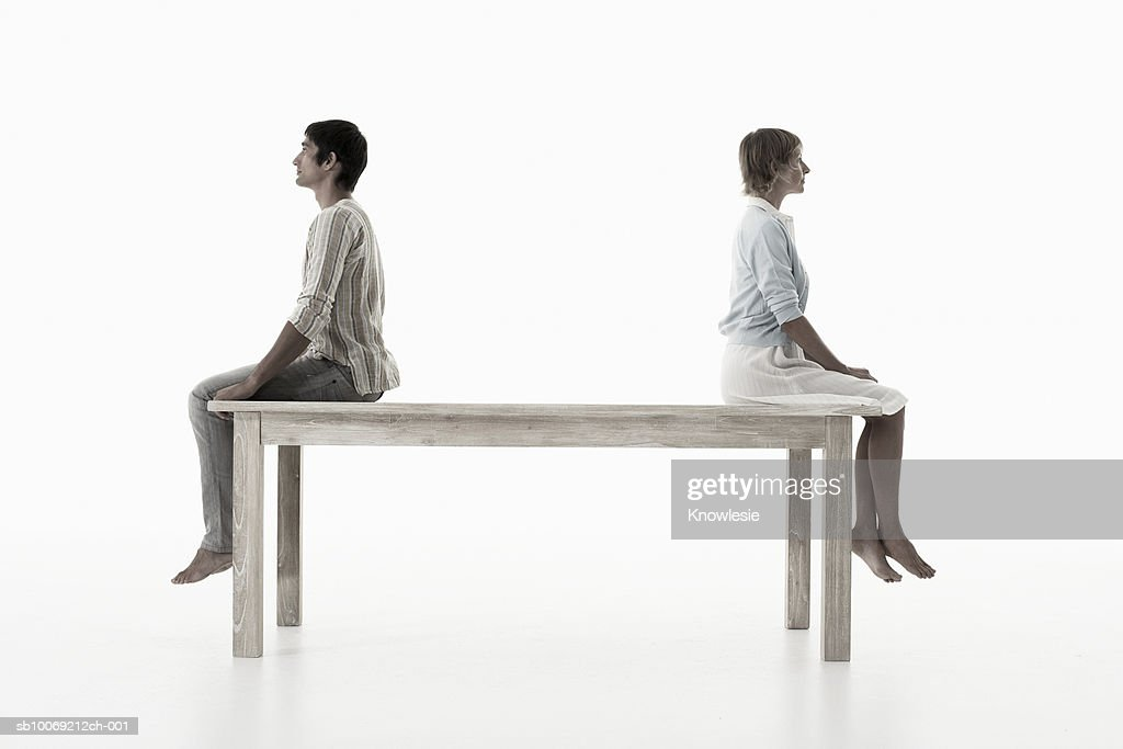 Couple sitting back to back on wooden table against white background, side view : Stockfoto