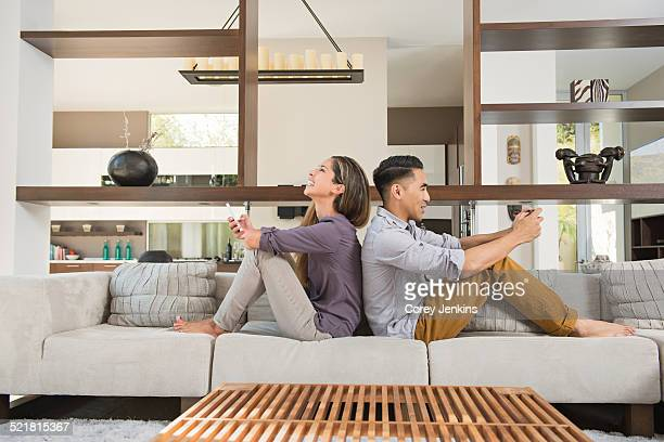 Couple sitting back to back playing games on smartphones on sitting room sofa