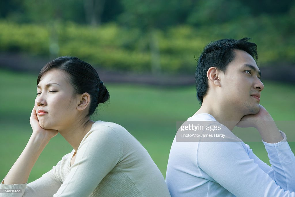 Couple sitting back to back, resting heads in hands : Stock Photo