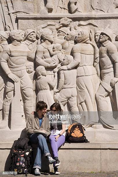 Couple sitting beside carved wall