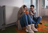 Couple sitting beside radiator